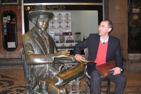 """Ângelo Cristóvão com a estátua de Fernando Pessoa no café """"A Brasileira"""" em Lisboa"""